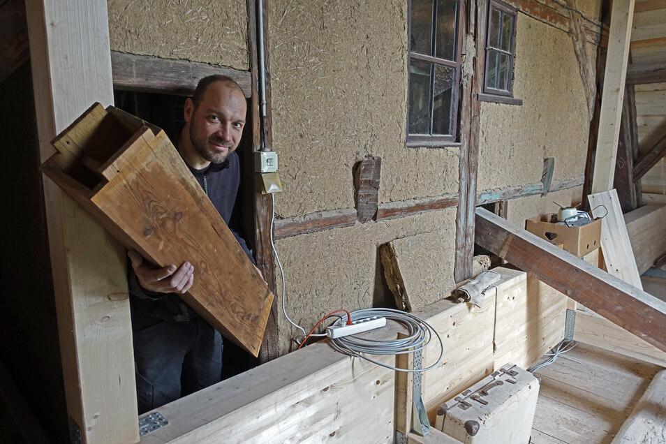 Orgelbauer Felix Tibussek schaut aus der Tür der Balgkammer. Mächtige Leimbinder fangen den Einbau unter dem Dach ab.