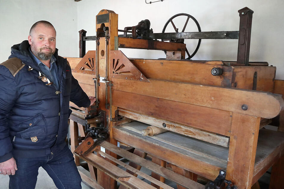 Torsten Heider, Mitarbeiter der Gemeinde Lohsa, zeigt die historische Wäscherolle im Gebäude neben dem Kindergarten Lohsa. Sie soll bald wieder in Betrieb gehen.