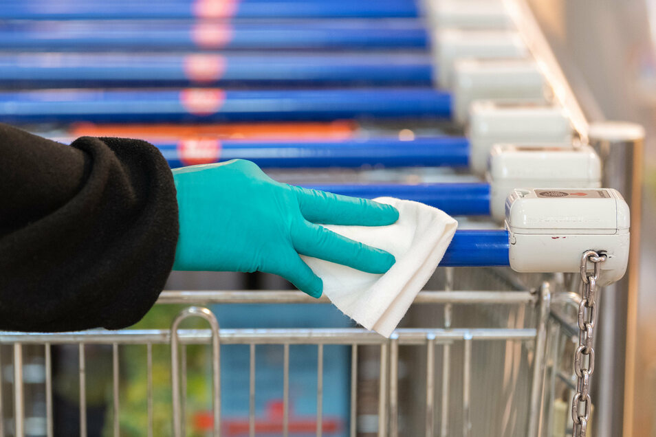 Mit Handschuh und Desinfektionsmittel: Zu Beginn der Pandemie setzten viele sächsische Einzelhändler noch Wachleute an den Eingängen ein. Angestellte in den Läden hätten sie gerne wieder.