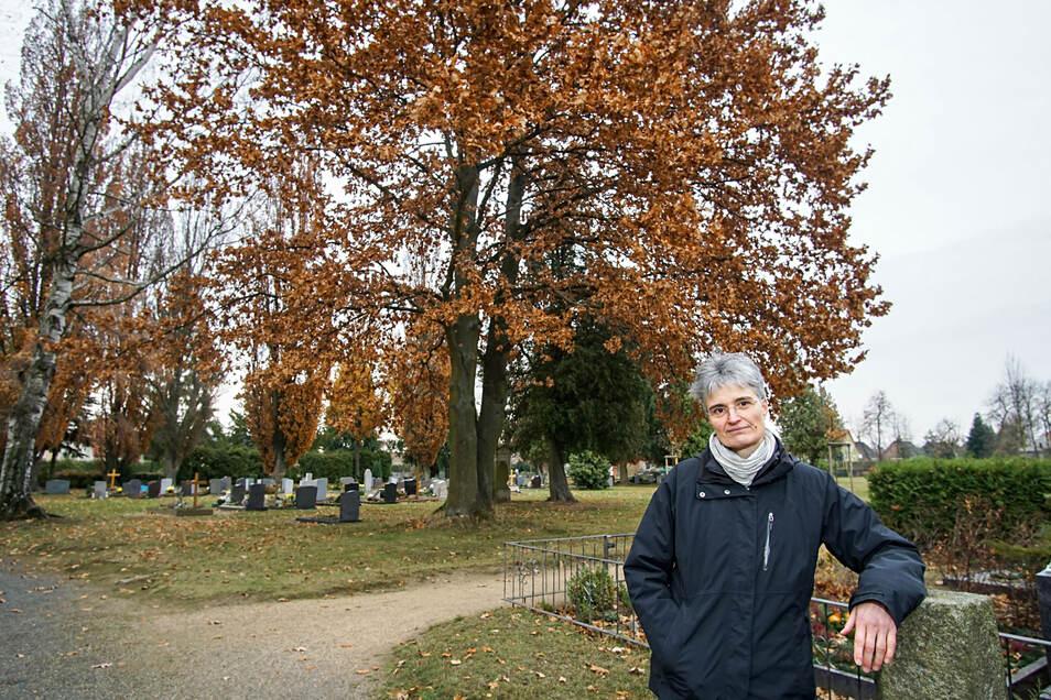 Pfarrerin Susanne Aechtner steht hier am Rand einer Urnen-Gemeinschaftsanlage auf dem Friedhof in Neschwitz. Rund um die große Eiche hinter ihr soll demnächst Platz für Baumbestattungen geschaffen werden.