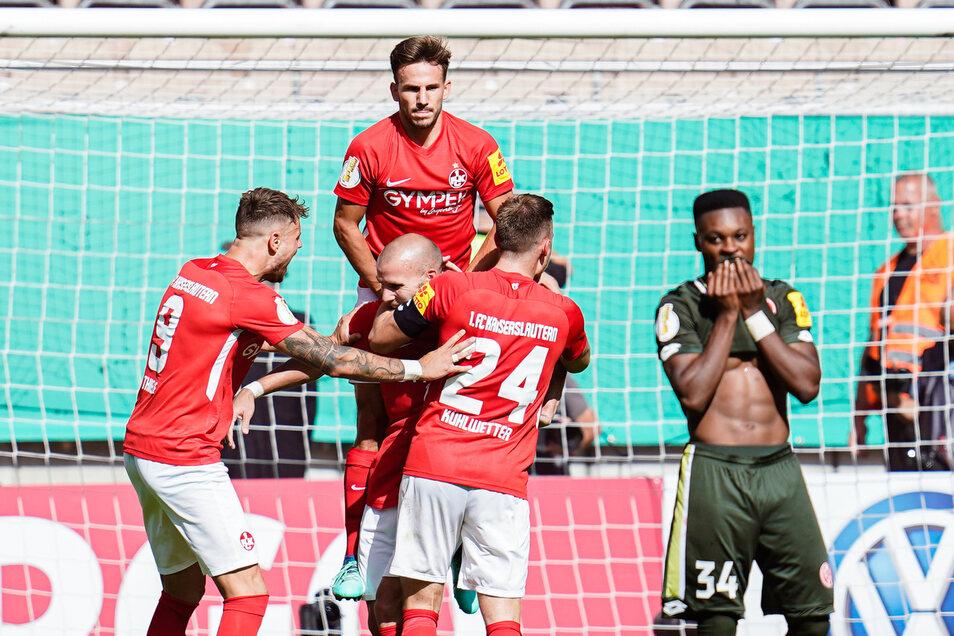 Kaiserslauterns Elfmeter-Torschütze Manfred Starke (M) jubelt mit Mannschaftskollegen über das Tor zum 1:0. Der Mainzer Ridle Baku ist fassungslos.