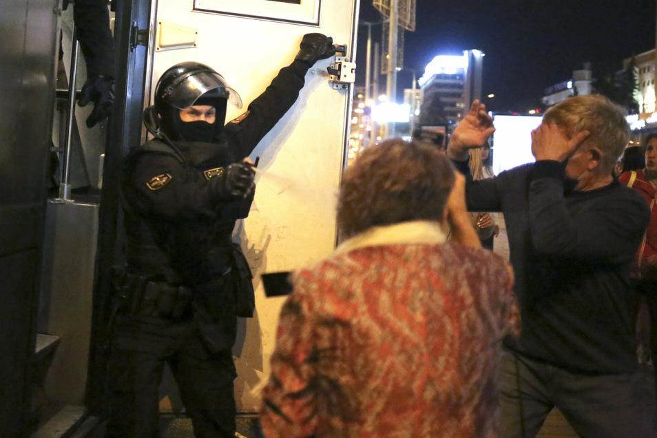 Ein Polizist setzt Pfefferspray gegen Demonstranten während einer Kundgebung in Minsk ein.