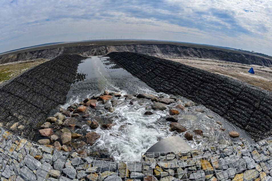 Wasser strömt über das Einlaufbauwerk in den ehemaligen Braunkohletagebau Cottbus-Nord. Die gesamte Landmasse bis zu den Windrädern im Hintergrund soll später einmal von Wasser bedeckt sein.