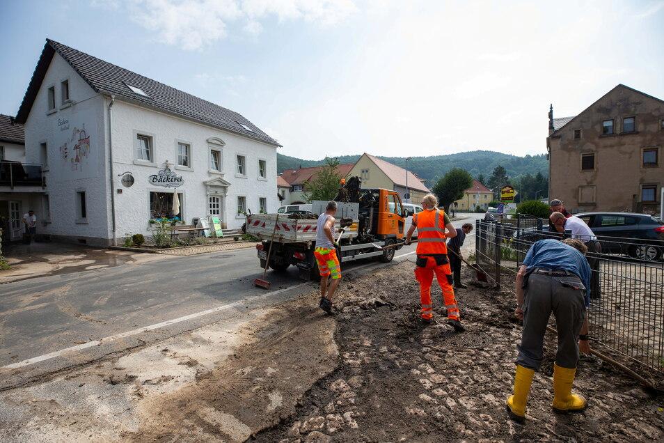 Fast alle Jahre wieder: Mitarbeiter des Pirnaer Bauhofes beseitigen im Juli 2019 die Überreste der Schlammlawine, die das Zentrum in Neundorf überrollte.