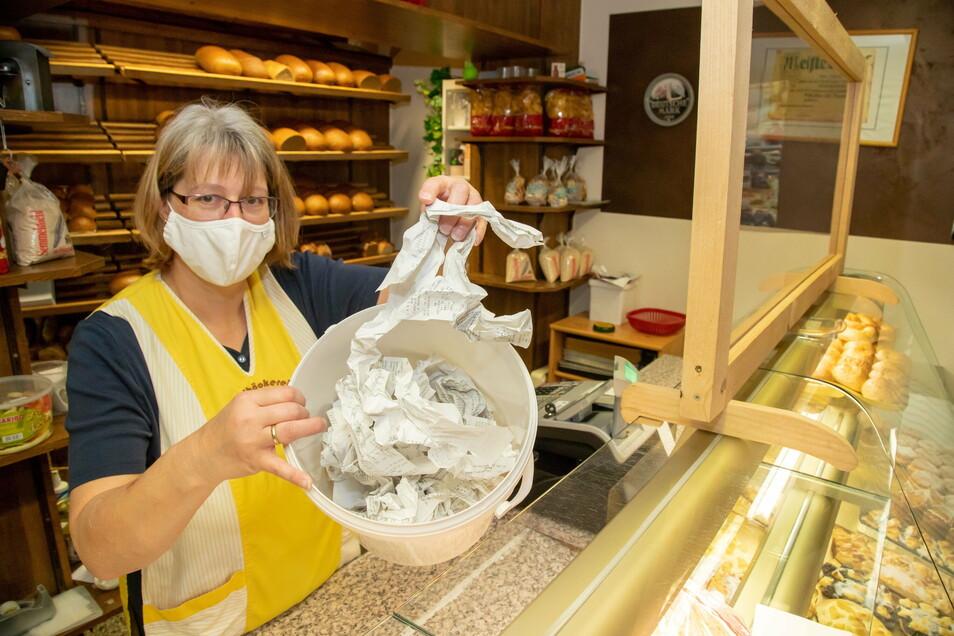 Claudia Schönig zeigt in der Bäckerei Kopke in Förstgen den Papiermüll, der durch die Bonpflicht jeden Tag entsteht.