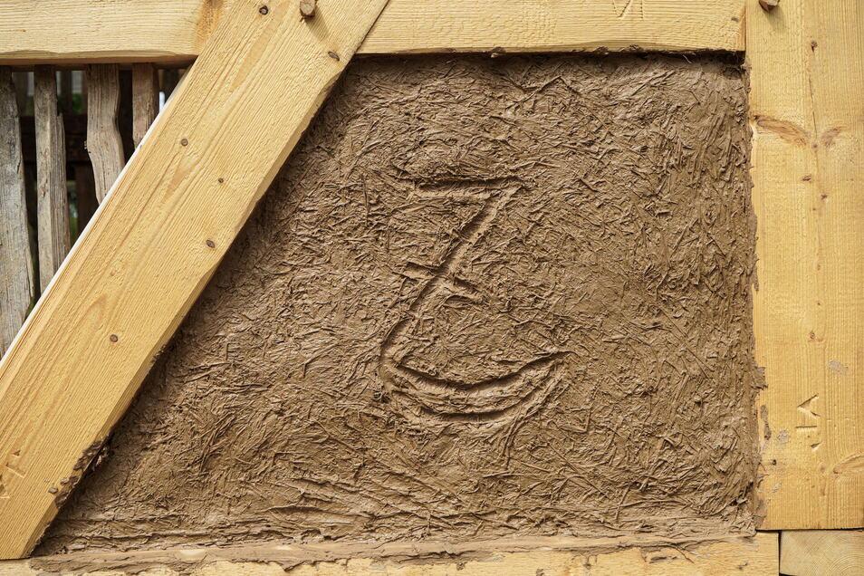 Die Sense - das Berufszeichen der Scharfrichter - hat Arnd Matthes in den frischen Lehm gezeichnet. Aus historischer Zeit wurde ein ebensolches Zeichen gerettet. Es wird am neuen Standort an der originalen Stelle wieder eingepasst.