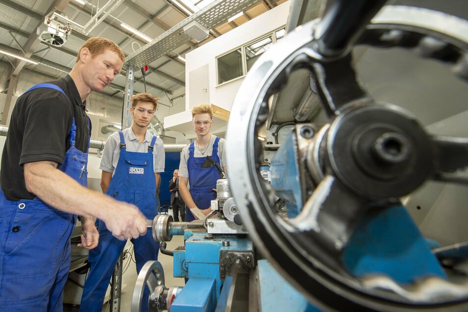 Neue Maschinenhalle im Bildungszentrum Pirna: Ausbilder Thomas Werner (l.) erklärt den Industriemechaniker-Azubis Tom Behrendt und Felix Kazimiers (r.) eine Drehmaschine.