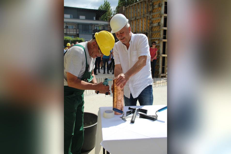 Schulleiter Frank Haubitz (r.) verschließt gemeinsam mit dem Polier die Zeitkapsel, die mit dem Grundstein eingemauert wird.