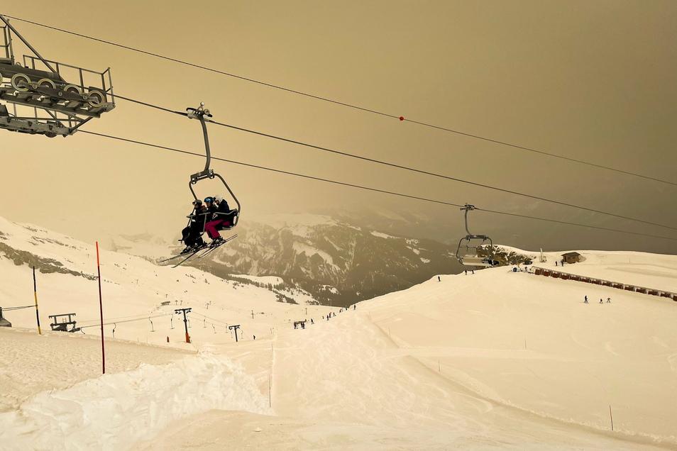 Skifahrer mit Gesichtsschutzmasken sitzen auf einem Sessellift, während Saharasand den Schnee und den Himmel orange färbt und eine besondere Lichtstimmung erzeugt.