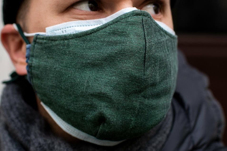 Doppelt schützt besser: Eine übergezogene Alltagsmaske drückt die OP-Maske ans Gesicht und kann so deren Filterleistung erhöhen.