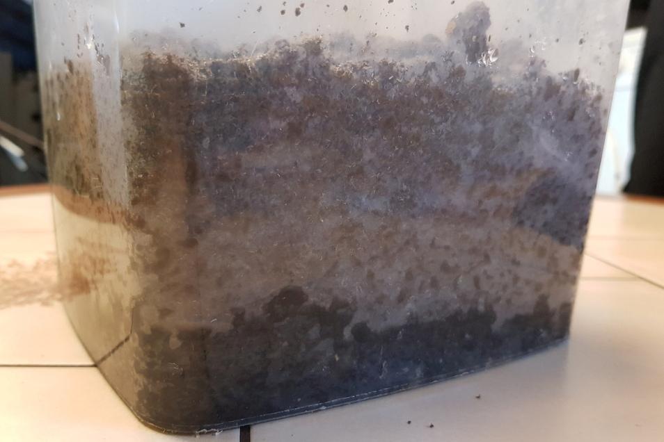 Bei der Besichtigung eines anderen Klärschlammlagers hat Olaf Dutschmann eine Probe des abgelagerten Materials mitgenommen. Die Konsistenz erinnert an Knete, der Geruch ist chemisch. Die in der Masse enthaltene Feuchtigkeit sammelt sich an der Unterseite.