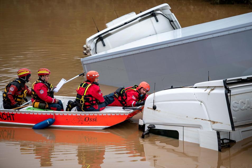 Helfer der Wasserwacht untersuchen von einem Boot aus Lastwagen. Auch Helfen aus Sachsen haben sich auf den Weg in die Katastrophenregion gemacht.