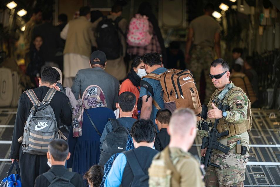 Ein US-Luftwaffenangehöriger (r)sorgt für Sicherheit, als afghanische Flüchtlinge während der Evakuierung vom Hamid Karzai International Airport im Rahmen der Operation Allies Refuge an Bord eines Militärtransportflugzeugs von Typ Boeing C-17 Globemaster