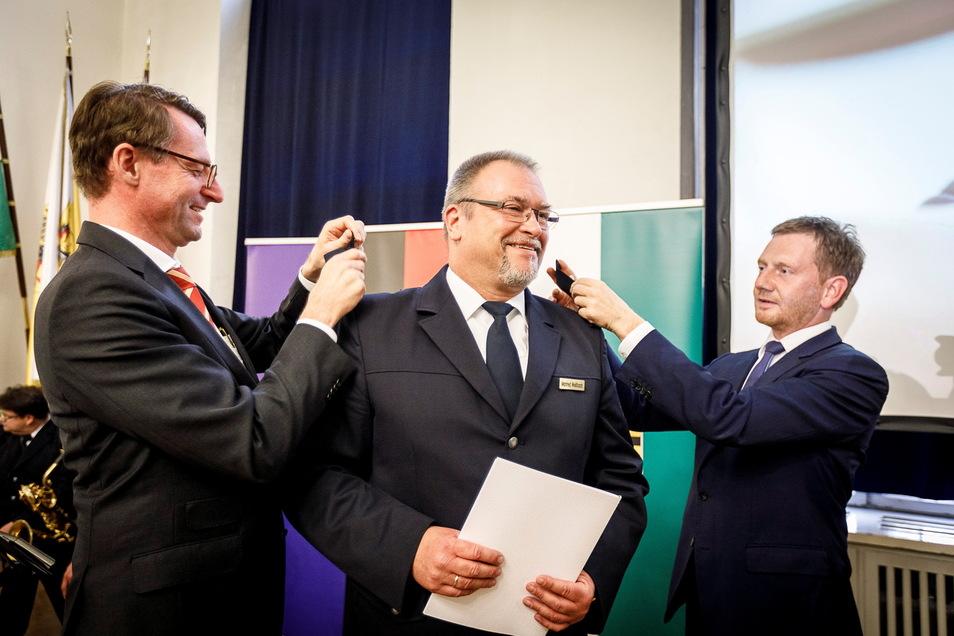 Hier bekommt der aktuelle Polizeipräsident 2019 seine neuen Schulterstücke: Der Sächsische Innenminister Roland Wöller (links) und Ministerpräsident Michael Kretschmer (rechts) bringen sie Manfred Weißbach an.