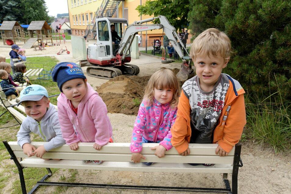 Noch ist nicht viel zu sehen von der Hangrutsche im Garten. Die Mitarbeiter der Ostritzer Firma Holzgestalten bereiten mit einem Bagger den Untergrund vor. Lino, Evelyn, Kimberly und Fabricio (v.l.) freuen sich schon und beobachten die Arbeiten.