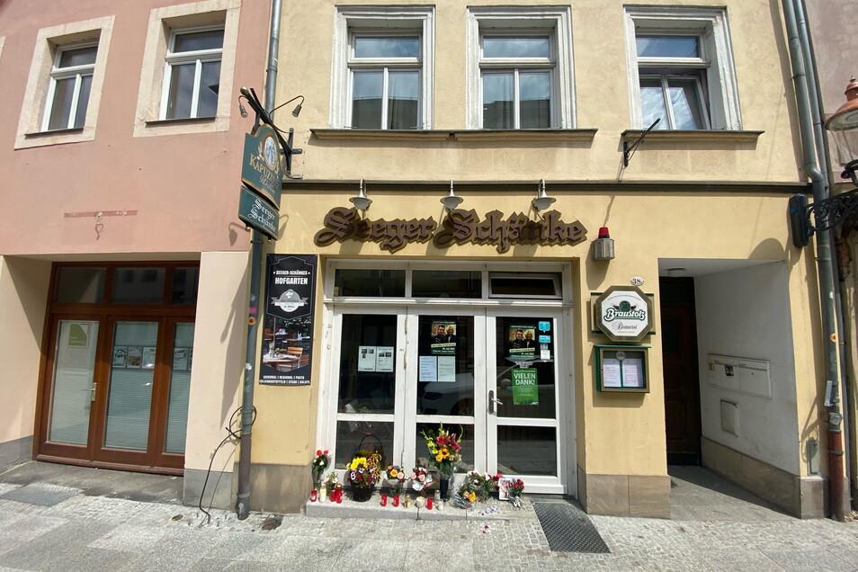 Vor der Seeger-Schänke in der Inneren Weberstraße in Zittau sind erste Trauerbekundungen zu sehen.