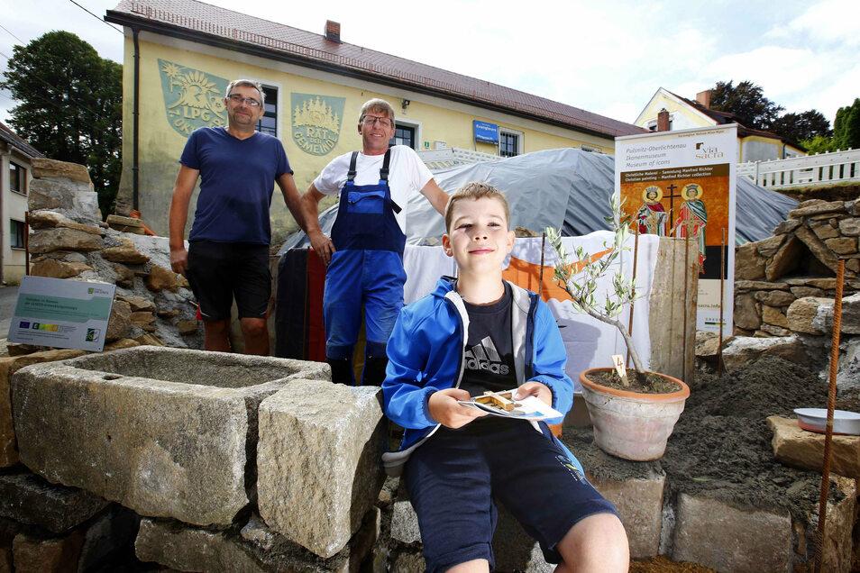 Vincent, der Sohn von Bauleiter Sandro Worowsky, zeigt, was in die Schatulle für die Grundsteinlegung des Tochni-Brunnens in Oberlichtenau kommt. Klaus Wenzlaw und Stephan Rachel von der ausführenden Firma UBK schauen interessiert zu.
