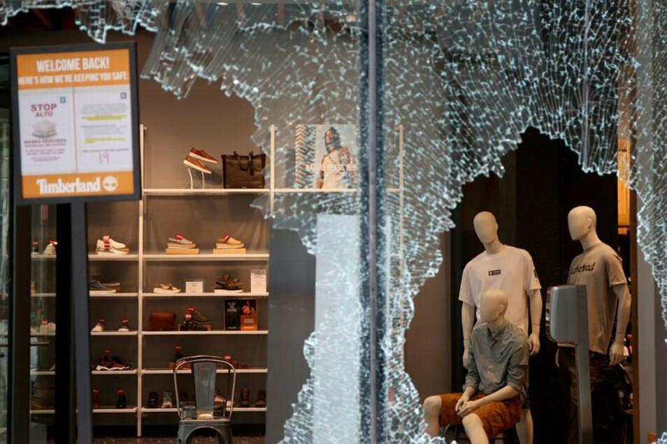 Die Scheibe eines Schaufenstergeschäfts ist nach Plünderungen zerbrochen.