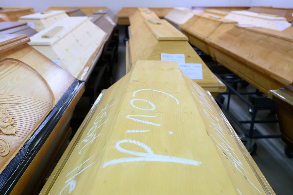 """Mit Kreide geschrieben steht """"Covid"""" auf einem Sarg mit einem Verstorbenen, der an oder mit dem Coronavirus gestorben ist, im Krematorium Dresden-Tolkewitz."""