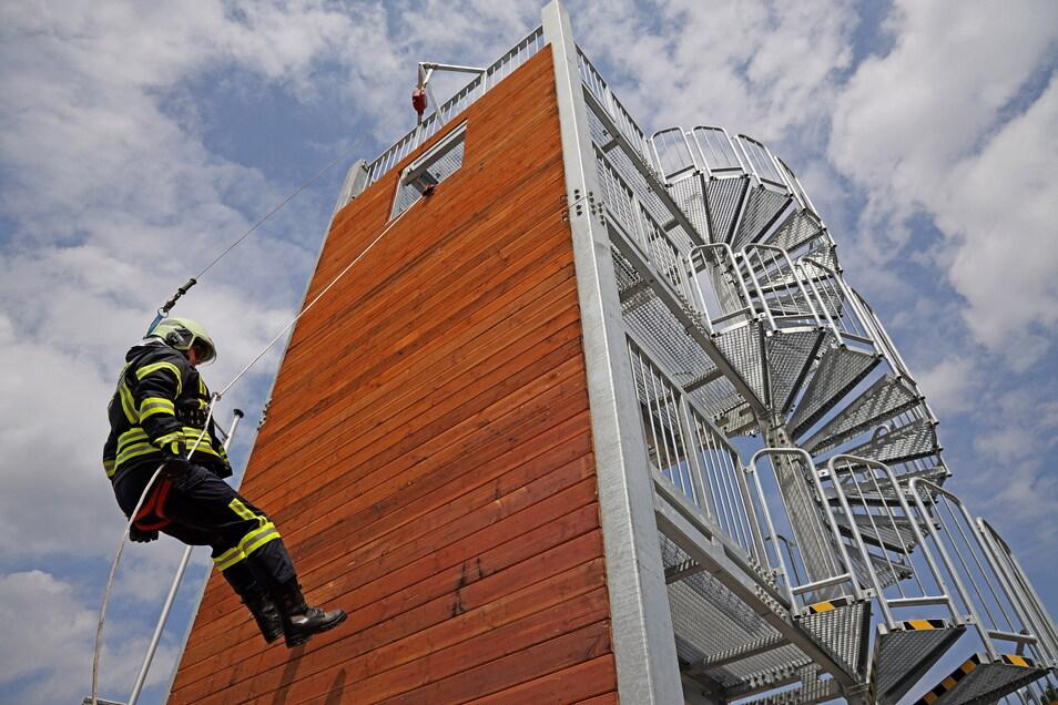 Gruppenführer Matthias Streiber demonstriert das Abseilen vom neuen Übungsturm aus acht Meter Höhe. Dieser Turm, auf dem auch das Retten über Treppen und aus Abwasserschächten trainiert werden kann, sucht im Landkreis Meißen seinesgleichen.