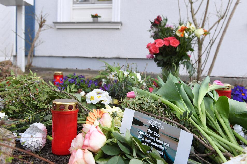 Kerzen und Blumen stehen vor dem Eingang des Hauses in Zinnowitz, in dem am 19. März 2019 eine 18-jährige Frau tot aufgefunden wurde.