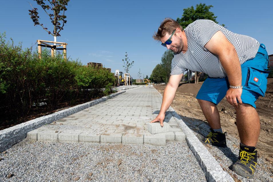 Letzte Arbeiten am Fußweg neben dem neuen Pendlerparkplatz am Radeberger Bahnhof. David Beyer von der Firma der Firma Steinsetz und Straßenbau Jens Hausdorf ordnet die Pflastersteine.