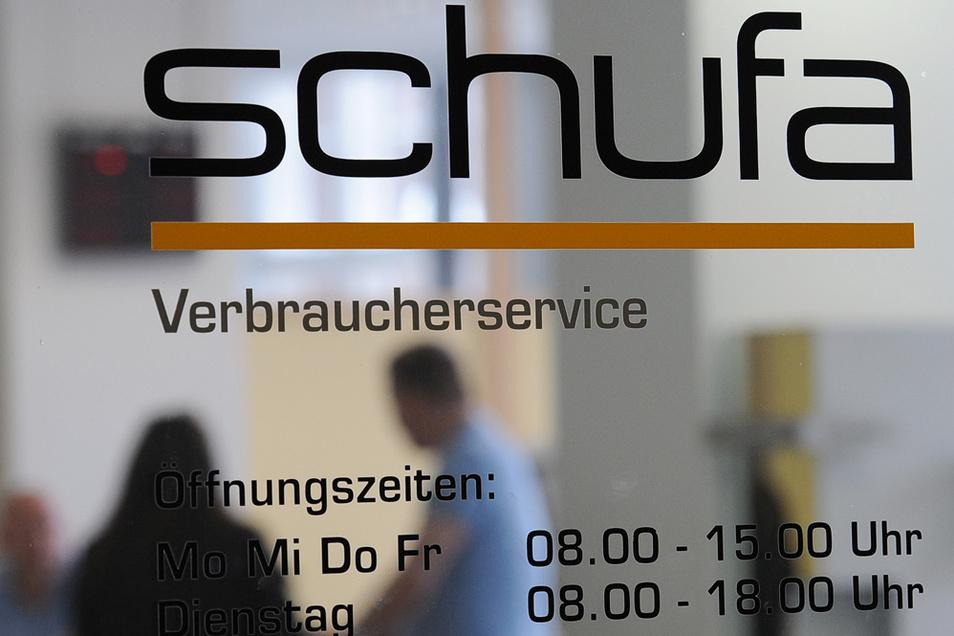 Ein Paar steht in einer Geschäftsstelle der Schufa Holding AG. Experten schlagen Alarm, weil die Schufa derzeit versucht, Einblick in private Konten zu bekommen.