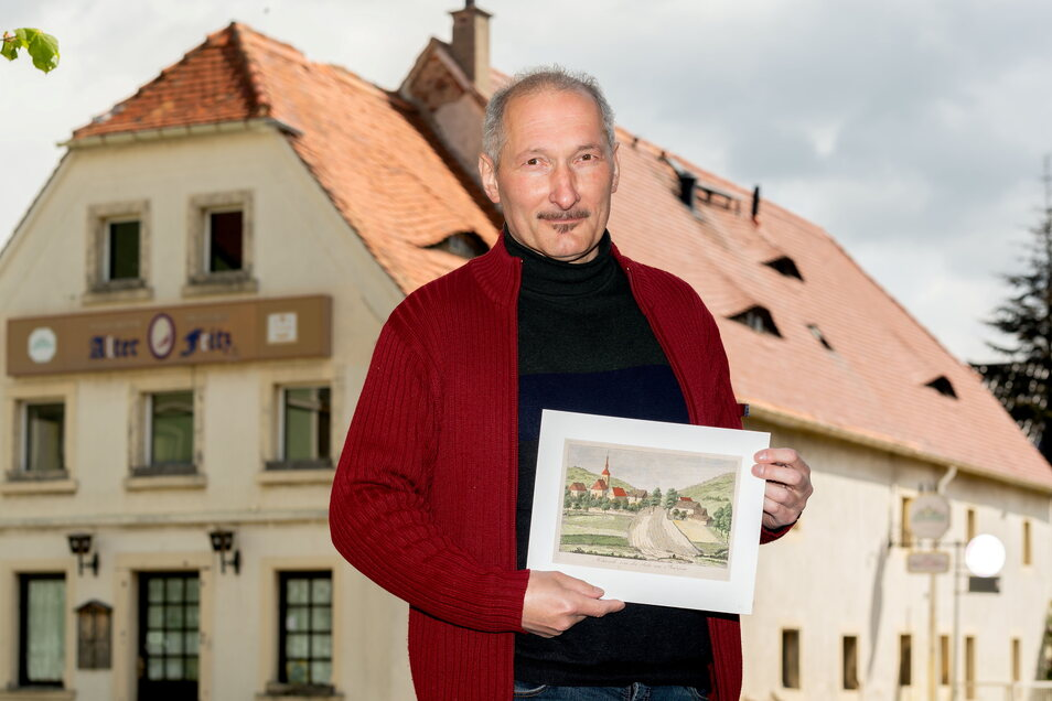 """Arndt Matthes ist der zweite Vorsitzende des Kulturhistorischen Vereins """"Alter Fritz"""" aus Hochkirch. Die colorierte Zeichnung in seinen Händen zeigt Hochkirchs Ortskern in einer Zeit, als die B 6 vermutlich gerade im Entstehen war."""