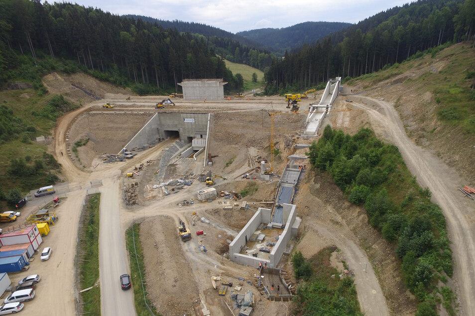 Dieses Luftbild zeigt den fertig aufgeschütteten Damm von der Luftseite aus mit den Durchlässen in der Mitte sowie dem Überlauf an der rechten Seite.