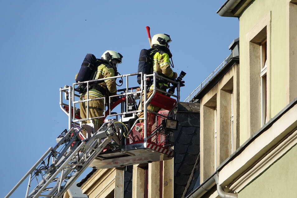Feuerwehrleute vor der Wohnung im Dachgeschoss des Mehrfamilienhauses.