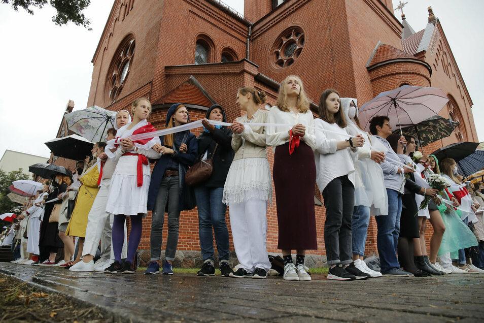 """Demonstrantinnen stehen während einer Kundgebung mit einem """"Warteband"""", einem Symbol des Protests, vor der Kirche der Heiligen Simon und Helena in Minsk."""