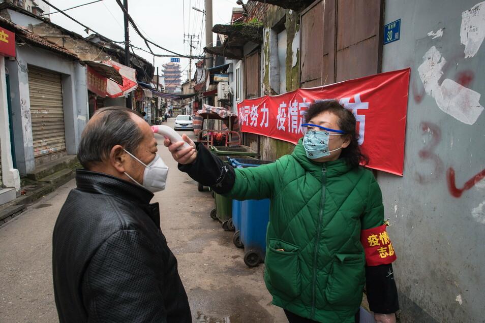 Eine Gemeindemitarbeiterin misst die Körpertemperatur eines Passanten in Wuhan, Anfang Februar 2020. In der zentralchinesischen Metropole war Sars-CoV-2 vor gut einem Jahr erstmals entdeckt worden.