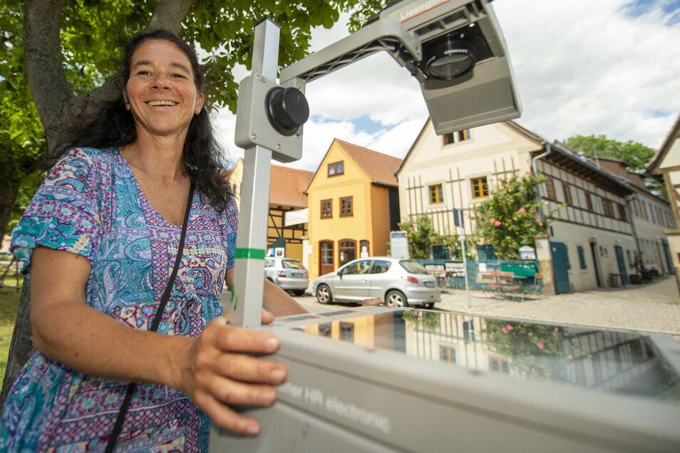 Funktioniert wie früher in der Schule, nur mit stärkerem Licht: Illuminationskünstlerin Claudia Reh wirft am Samstagabend bunte Kunstwerke mit Projektoren an die Häuserwände auf dem Dorfanger.