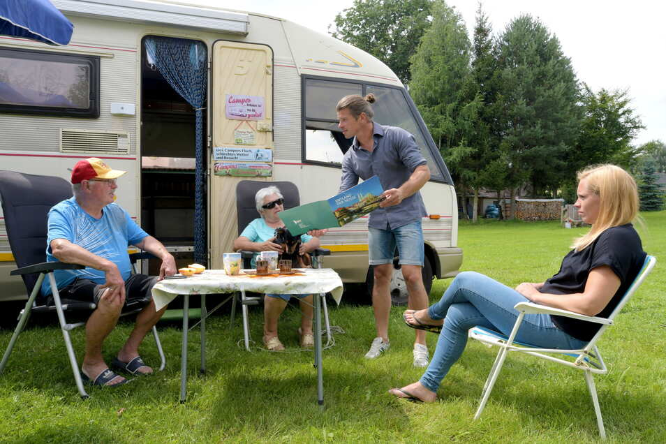 Campingplatzbetreiber André Scholze (stehend) und seine Lebenspartnerin Christina Wienecke (rechts) kommen gern mit ihren Gästen ins Gespräch, wie hier mit Brigitte und Frank Jentsch aus Zittau.