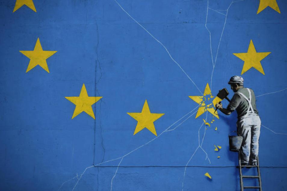 Dieses Brexit-Wandbild des britischen Streetartkünstlers Bansky hängt in der englischen Küstenstadt Dover. Es zeigt einen Mann, der die EU-Flagge mit einem Hammer entfernt.