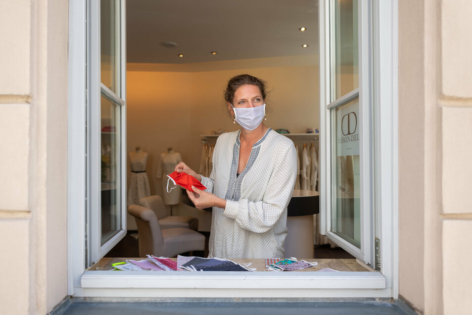 Die Designerin Dorothea Michalk verkauft am Fenster ihres Ateliers Stoffmasken aus der eigenen Schneiderwerkstatt.