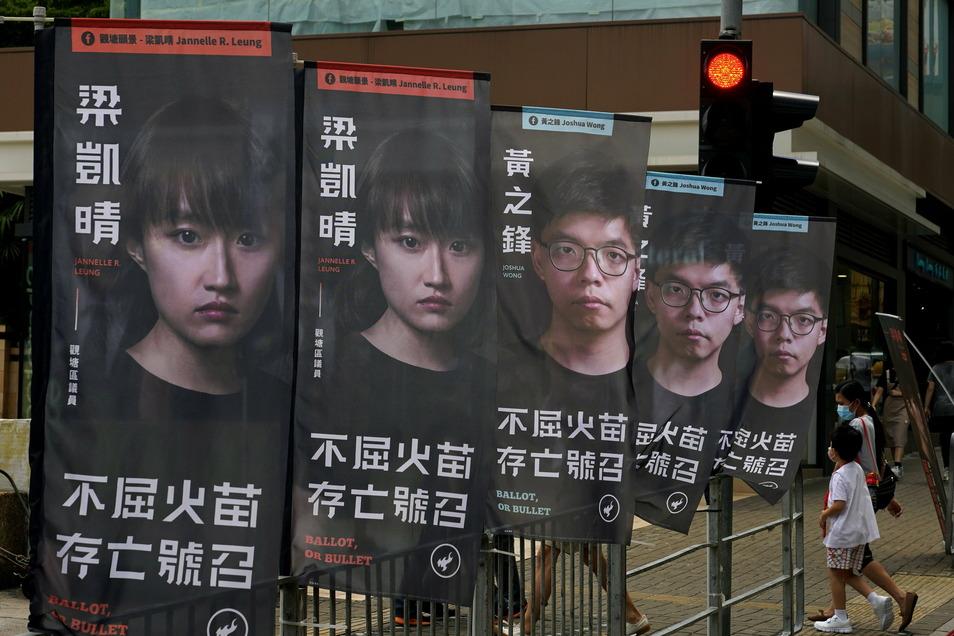 Banner des prodemokratischen Kandidaten Joshua Wong (rechts) sind vor einer U-Bahn-Station zu sehen. Der Aktivist sitzt derzeit in Haft.