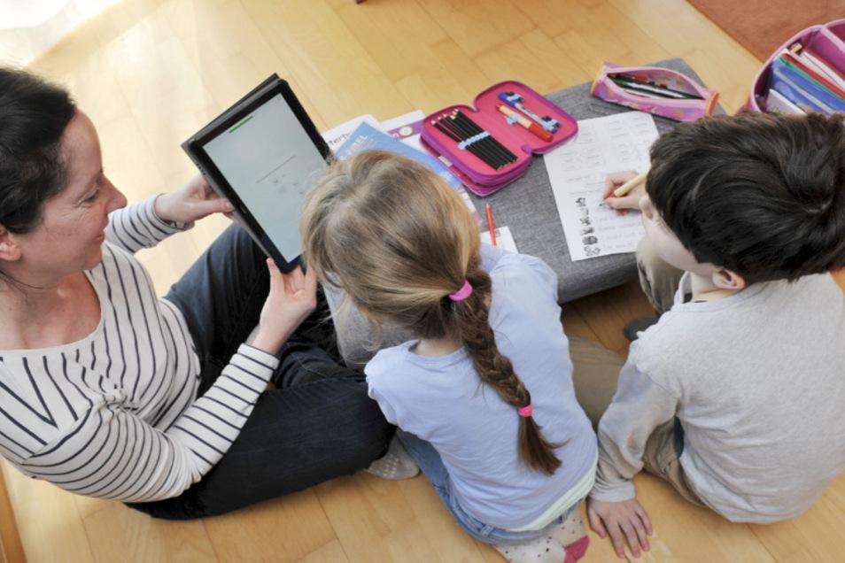 Jana Schulz im Homeoffice mit ihren Kindern Helene und Hannes. Gemeinsam gehen sie die Aufgaben am Tablet durch.
