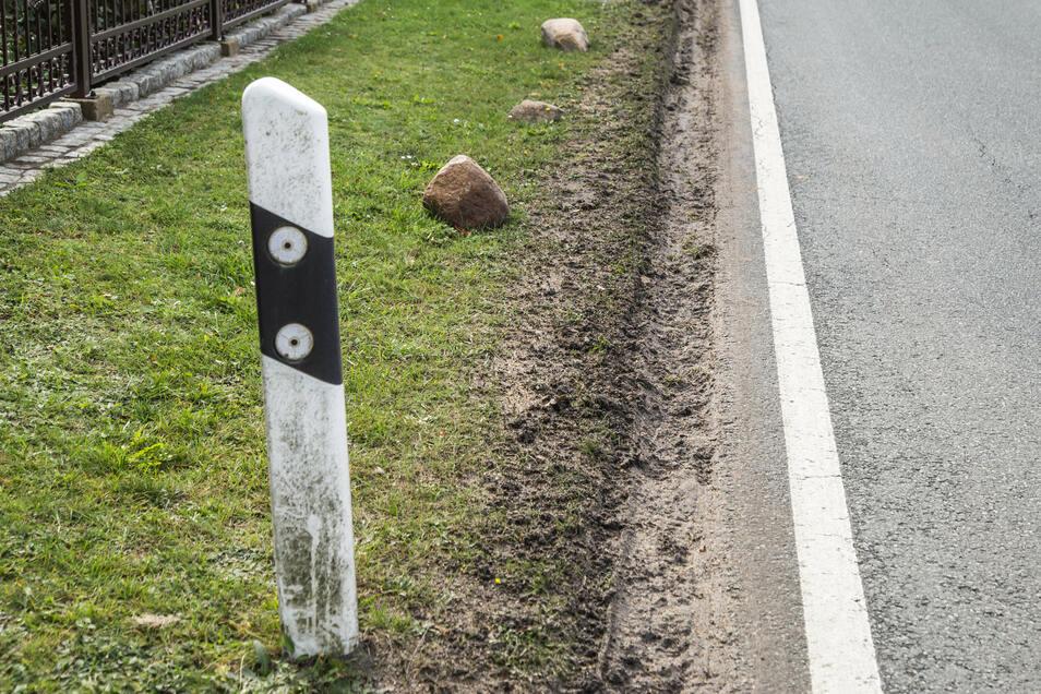 Würden die Begrenzungspfähle und Steine nicht sein, die Autos kämen noch dichter am Grundstück der Familie Bille vorbei. Ursprünglich reichte der Rasen bis an den Asphalt heran.