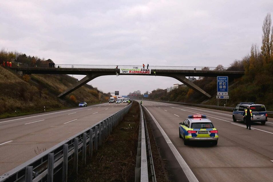 Zwei Menschen haben sich neben dem Spruchband an die Brücke gehängt.