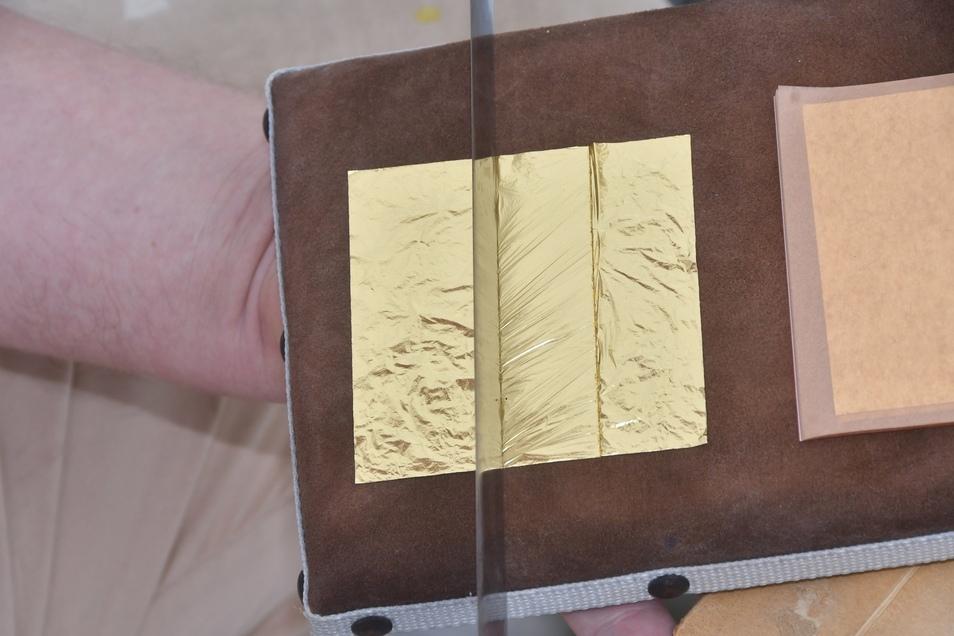Im nächsten Schritt wird das zarte Gold passend mit dem Vergoldemesser zugeschnitten.