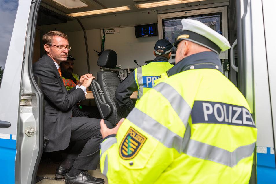 Innenminister Roland Wöller (CDU, l) spricht bei einer Kontrolle am Rastplatz Dresdner Tor an der A4 mit Polizeibeamten.
