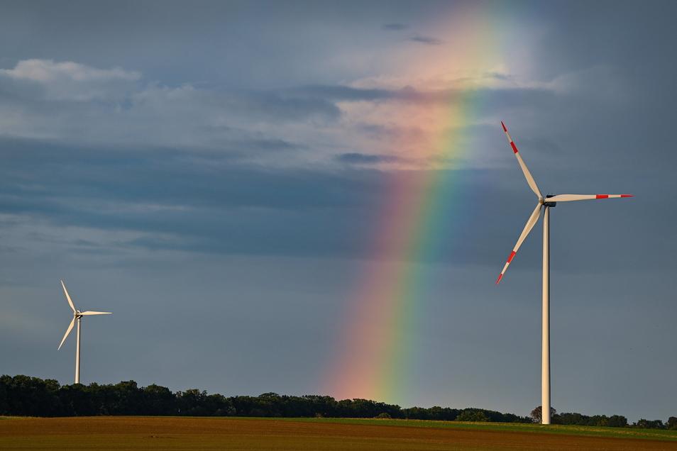 Ein Regenbogen spannt sich über zwei Windenergieanlagen in einem Windpark im Landkreis Oder-Spree. Deutschland will bis 2045 nur noch so viel Treibhausgas ausstoßen, wie auch wieder gebunden werden kann.