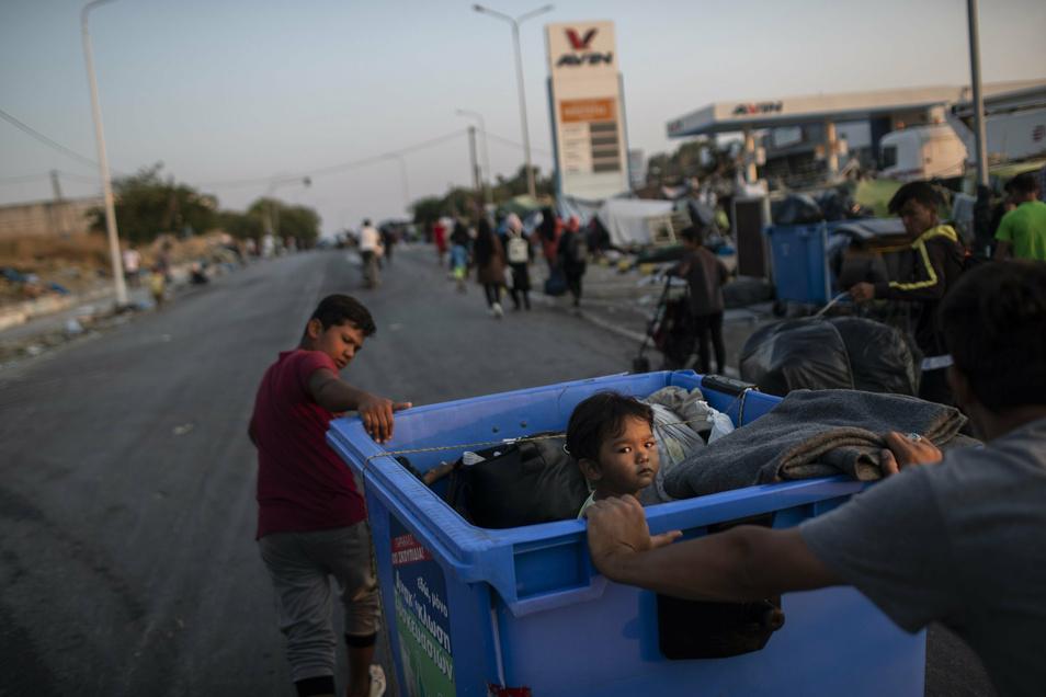 Ein Junge (l) zieht einen Müllcontainer, in dem ein Kind sitzt. Migranten gehen in großen Gruppen ins neue Lager von Lesbos.