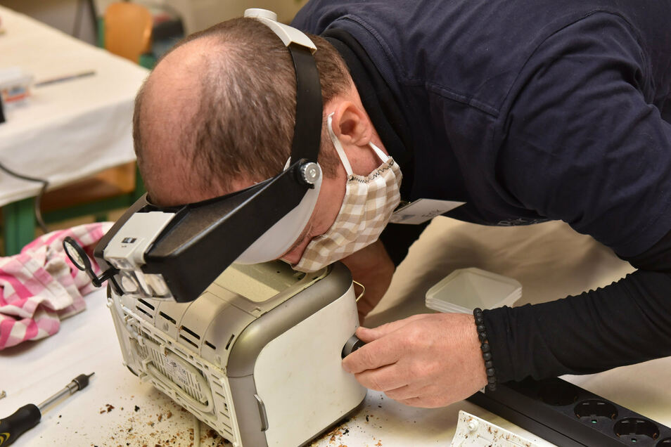 Erik Schanze vom Repair-Café beugt sich über den kaputten Toaster - ist das Gerät noch zu retten?