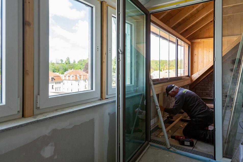 Norbert Müller vom Holzbau Dresden beim Arbeiten in einer Dachwohnung, die einen schönen Blick ins Erzgebirge bietet.