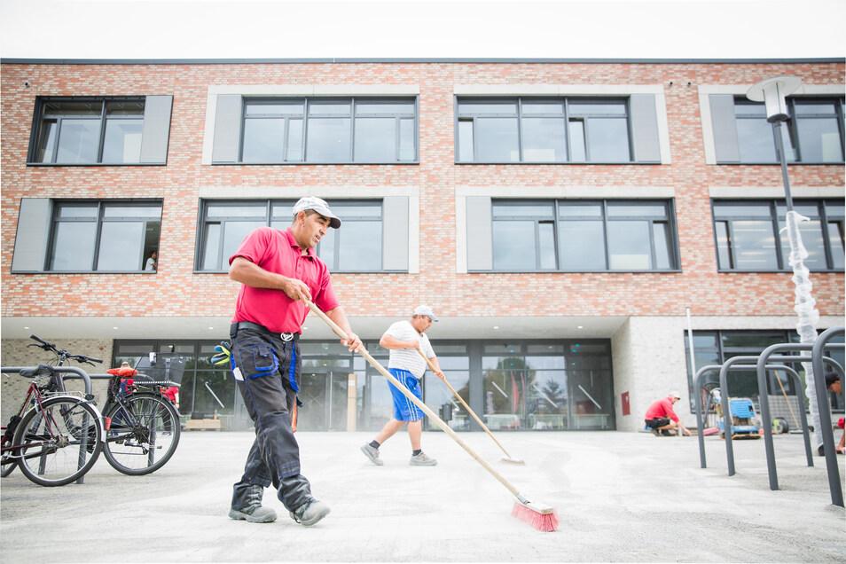 Auf der Zielgeraden wuseln noch einmal zahlreiche Bauleute über den neuen Schulcampus an der Gehestraße in Pieschen. Er gilt als Sachsens größter Schulcampus.