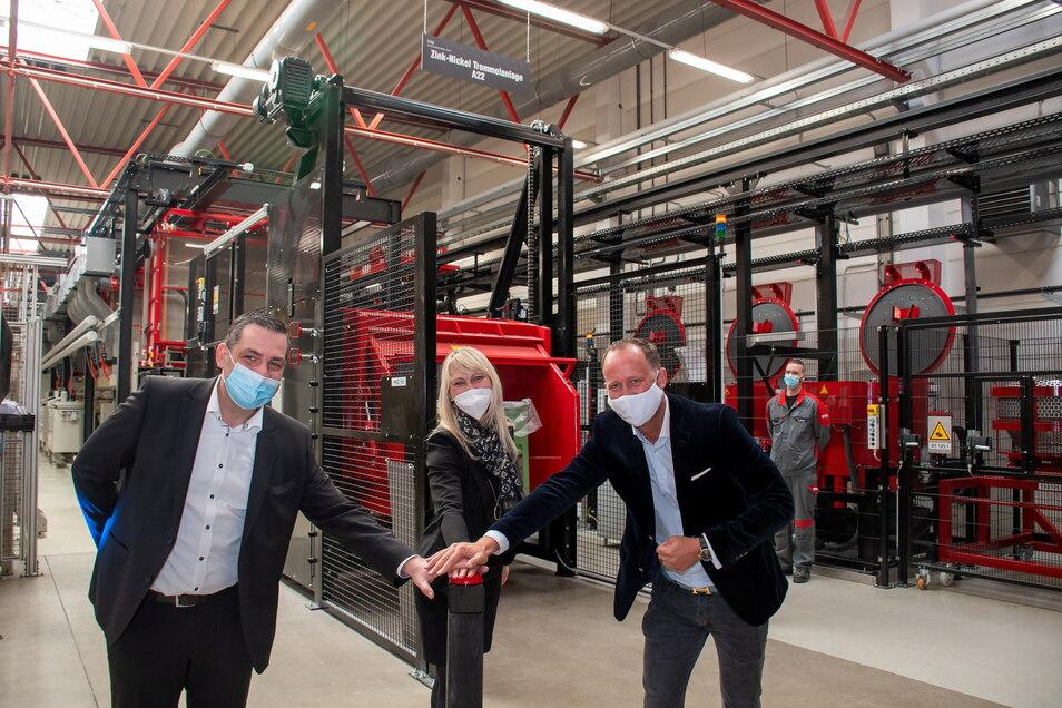 Marko Lietzke, Geschäftsführer der Firma Metallveredlung Döbeln (von links), Katrin Möckel und Nicolai A.J. Baum, Geschäftsführer der KAP Surface Technologies, starten die Produktion in der neuen Zink-Nickel-Trommel-Anlage.