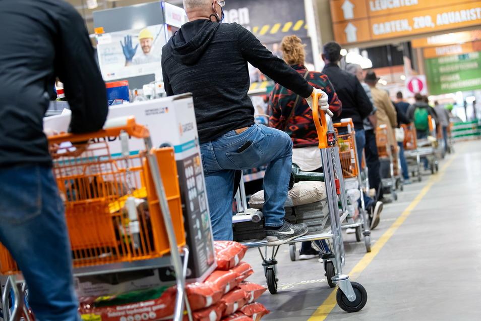 Kunden stehen mit Einkaufswagen in einem Hornbach-Baumarkt vor den Kassen an.