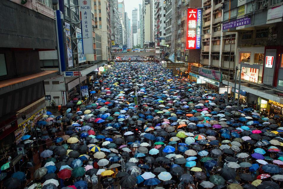 Demonstranten schützen sich mit Schirmen vor dem anhaltenden Regen. In der ehemaligen britischen Kronkolonie Hongkong sind die Proteste gegen den Einfluss aus Peking in eine neue Runde gegangen.